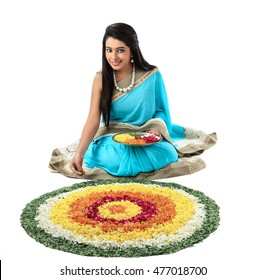 young Indian girl in traditional outfits making beautiful rangoli Indian festival, Happy ,diwal or Onam celebration.