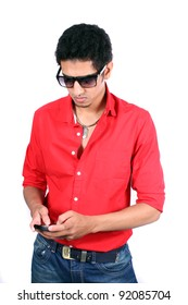A young Indian guy addicted to phone typing and sending messages over the cellphone,on white studio background.