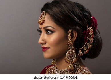 Young Indian lady with bridal wear, jewelry and make-up