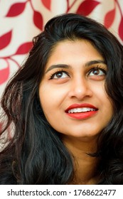 An young Indian lady with red lipstick and long hair posing looking upwards