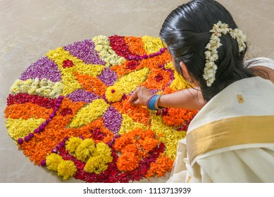 Young Indian Malayali woman putting Pookalam flower Rangoli floral decorations for Onam festival of Kerala India