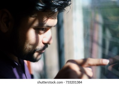 A young Indian male is seen looking outside a window into the sunlight.