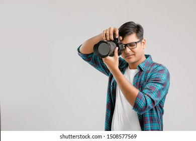 Young Indian man capturing photo with camera