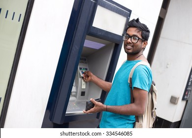 young indian man at the cashpoint withdrawing money
