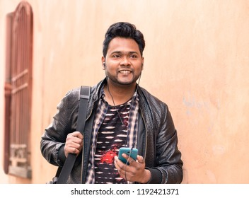 Young indian man holding mobile phone with earphones is walking  confident - Happy asian male using smartphone smiling and looking ahead - Concept of lifestyle  and tecnology with pink wall copy space