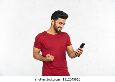 young Indian man holding phone and smiling