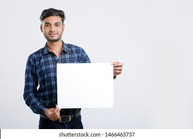 young indian man holding poster