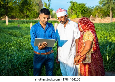 Young indian man with laptop showing something to village farmer family on internet standing in green field, agriculture land, teaching computer and use of technology.