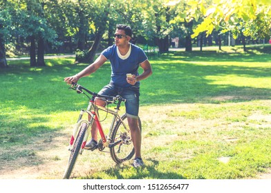 Young Indian man on bicycle with smartphone