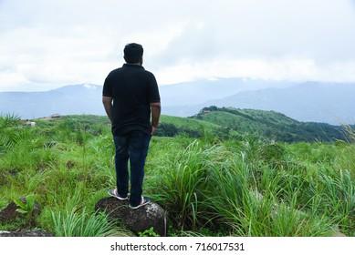 Young Indian man on top of mountain. Hiker climb on peak of rock above foggy valley at Munnar Idukki Kerala India. Successful man