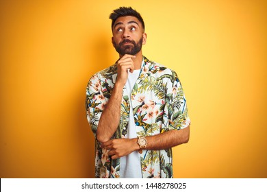 Young indian man on vacation wearing summer floral shirt over isolated yellow background with hand on chin thinking about question, pensive expression. Smiling with thoughtful face. Doubt concept.