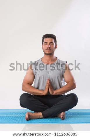 young indian man practicing yoga and meditation indoor