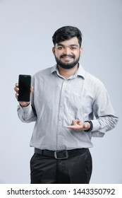 Young Indian man showing mobile screen