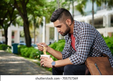 Young Indian man sitting outdoors and eating instant noodle soup for lunch