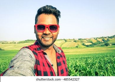 Young indian man taking selfie at green corn field with country hills background - Handsome african guy having fun using modern technology outdoors in a farmland - Vintage filter look soft vignetting