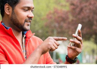 young indian man using cell phone with touch technology. young ethnic south asian man in the park texting with his smart phone close up view