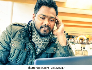 Young Indian man using laptop sitting at cafe table inside city building - Happy asian guy with pc chatting on line wifi connected - Concept of working with modern technologies and high tech devices