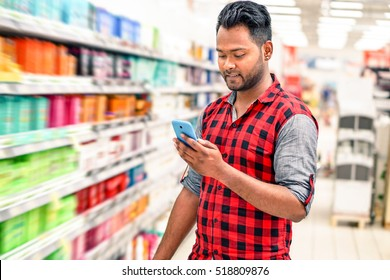 Young indian man using mobile in blurred store lane - Handsome happy guy holding smart phone and smiling inside shopping mall next to colorful bottles - Radial zoom defocus on supermarket products