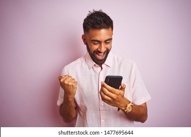 Young indian man using smartphone standing over isolated pink background screaming proud and celebrating victory and success very excited, cheering emotion