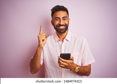 Young indian man using smartphone standing over isolated pink background surprised with an idea or question pointing finger with happy face, number one