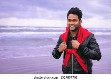 Young indian man walking on the beach on cloudy day background - Handsome asian guy smiling  in confident attitude hiking along the cost    - Concept of healthy male lifestyle - Soft blue filter image