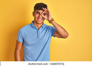 Young indian man wearing blue polo standing over isolated yellow background doing ok gesture with hand smiling, eye looking through fingers with happy face.