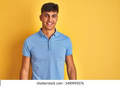 Young indian man wearing blue polo standing over isolated yellow background with a happy and cool smile on face. Lucky person.