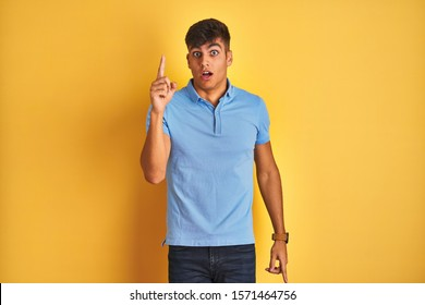 Young indian man wearing blue polo standing over isolated yellow background pointing finger up with successful idea. Exited and happy. Number one.