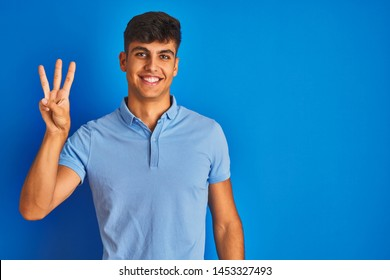 Young indian man wearing casual polo standing over isolated blue background showing and pointing up with fingers number three while smiling confident and happy.