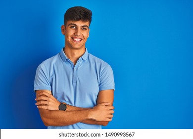 Young indian man wearing casual polo standing over isolated blue background happy face smiling with crossed arms looking at the camera. Positive person.