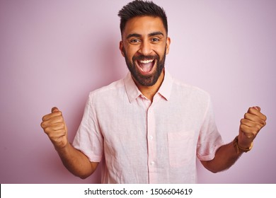Young indian man wearing casual shirt standing over isolated pink background celebrating surprised and amazed for success with arms raised and open eyes. Winner concept.