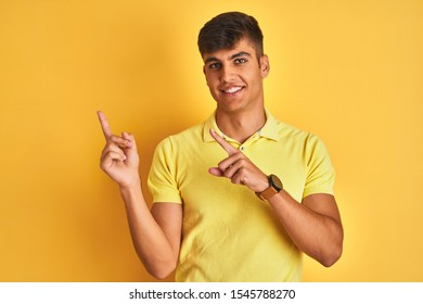 Young indian man wearing casual polo standing over isolated yellow background smiling and looking at the camera pointing with two hands and fingers to the side.