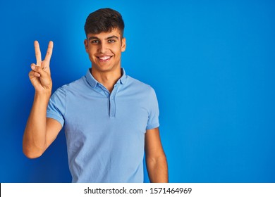 Young indian man wearing casual polo standing over isolated blue background showing and pointing up with fingers number two while smiling confident and happy.