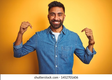 Young indian man wearing denim shirt standing over isolated yellow background looking confident with smile on face, pointing oneself with fingers proud and happy.