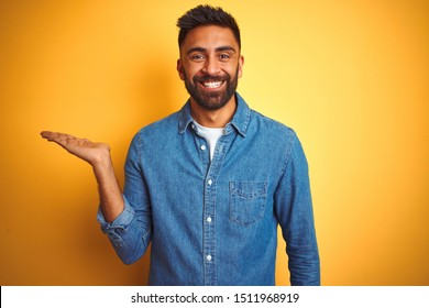 Young indian man wearing denim shirt standing over isolated yellow background smiling cheerful presenting and pointing with palm of hand looking at the camera.