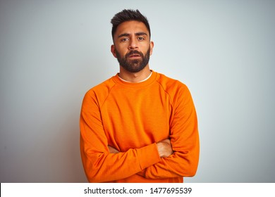 Young indian man wearing orange sweater over isolated white background skeptic and nervous, disapproving expression on face with crossed arms. Negative person.