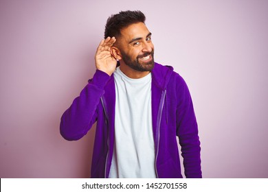 Young indian man wearing purple sweatshirt standing over isolated pink background smiling with hand over ear listening an hearing to rumor or gossip. Deafness concept.