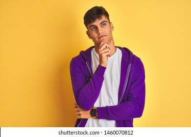Young indian man wearing purple sweatshirt standing over isolated yellow background with hand on chin thinking about question, pensive expression. Smiling with thoughtful face. Doubt concept.