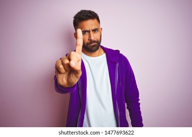 Young indian man wearing purple sweatshirt standing over isolated pink background Pointing with finger up and angry expression, showing no gesture