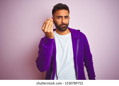 Young indian man wearing purple sweatshirt standing over isolated pink background Doing Italian gesture with hand and fingers confident expression