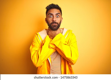 Young indian man wearing raincoat standing over isolated yellow background shouting and suffocate because painful strangle. Health problem. Asphyxiate and suicide concept.