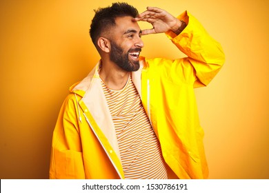 Young indian man wearing raincoat standing over isolated yellow background very happy and smiling looking far away with hand over head. Searching concept.