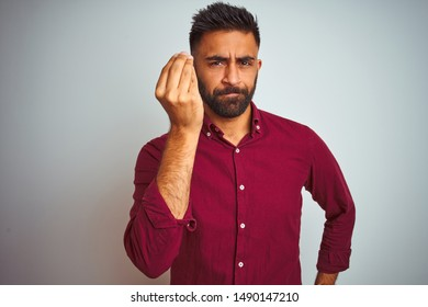 Young indian man wearing red elegant shirt standing over isolated grey background Doing Italian gesture with hand and fingers confident expression