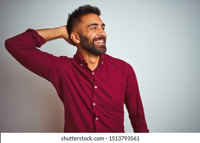 Young indian man wearing red elegant shirt standing over isolated grey background smiling confident touching hair with hand up gesture, posing attractive and fashionable