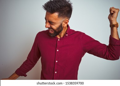 Young indian man wearing red elegant shirt standing over isolated grey background Dancing happy and cheerful, smiling moving casual and confident listening to music