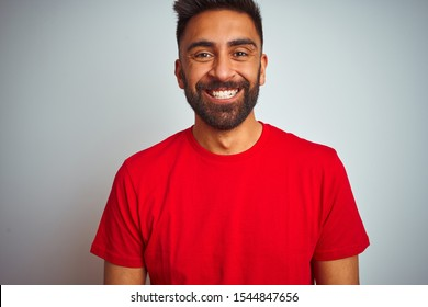 Young indian man wearing red t-shirt over isolated white background with a happy and cool smile on face. Lucky person.