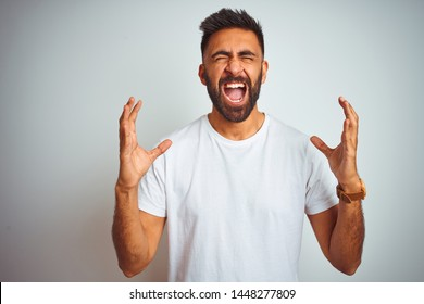 Young indian man wearing t-shirt standing over isolated white background crazy and mad shouting and yelling with aggressive expression and arms raised. Frustration concept.