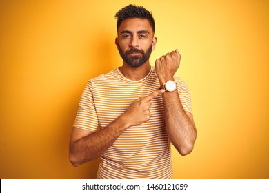 Young indian man wearing t-shirt standing over isolated yellow background In hurry pointing to watch time, impatience, looking at the camera with relaxed expression