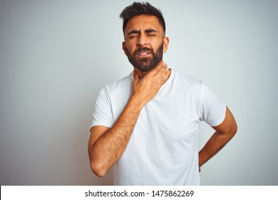 Young indian man wearing t-shirt standing over isolated white background Touching painful neck, sore throat for flu, clod and infection