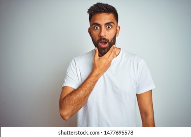 Young indian man wearing t-shirt standing over isolated white background Looking fascinated with disbelief, surprise and amazed expression with hands on chin